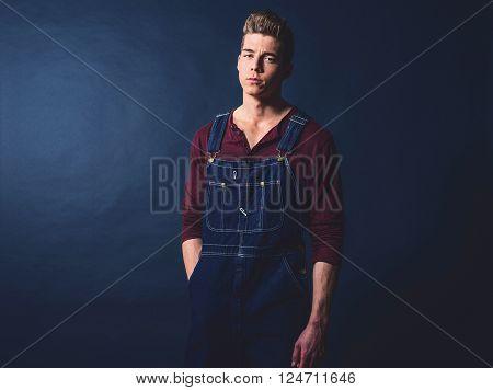 Retro 1950s worker fashion man wearing jeans bib and brace.