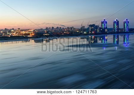 Scenic night landscape with the breaking of the ice on the river with a fast flowing on the background of city with lights and reflections in water shot on a long exposure