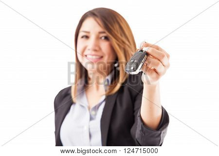 Closeup of a young female sales executive handing over some car keys to a customer. Focus on keys