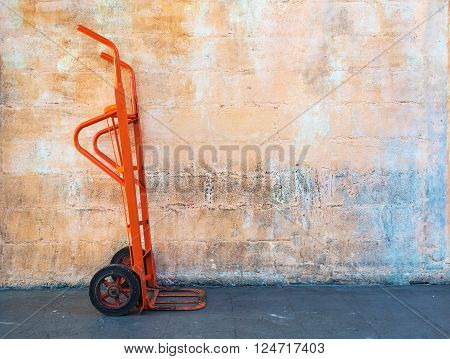 Red steel hand trolley (dolly) or sack truck against orange brick wall