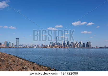 This image contains views of Jersey City and Manhattan as seen from Liberty State Park. From left to right you can see the Goldman Sachs Tower 432 Park Avenue Freedom Tower with Ellis Island in front and the Brooklyn Bridge on the fa