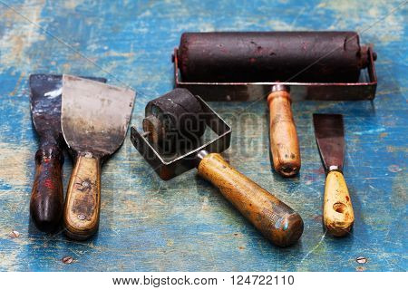 Vintage design artist tools: black rubber roller, big and small putty knives on blue paint wooden background. Diy tools, decorator accessories concept. soft focus