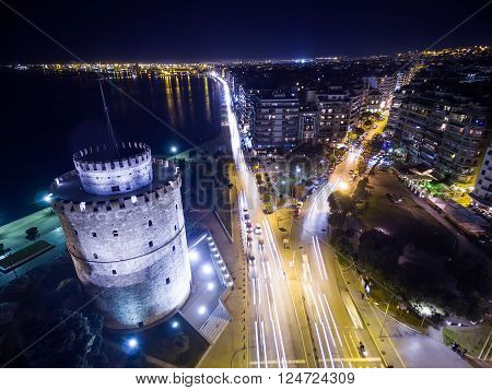 Aerial view of famous White Tower and the city of Thessaloniki at night Greece. Image taken with action drone camera causing distortion and blur.