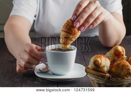 woman dipping croissant in coffee on wooden table