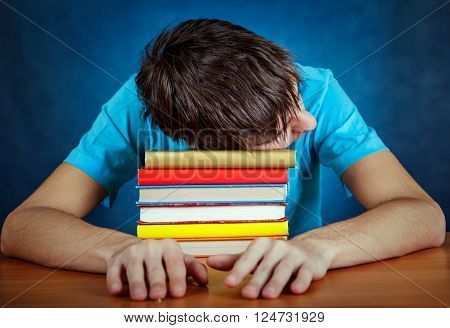 Tired Young Man sleep on the Books on the Blue Background
