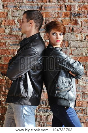 Uneasy Conversation - Couple Standing Next To A Brick Wall