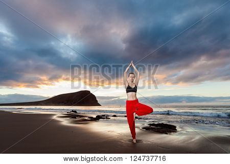 Summer sunrise yoga session on beautiful Playa de La Tejita beach with view on atlantic ocean and Punta Roja rock - tropical Tenerife island Canary in Spain. Vriksha-asana tree pose