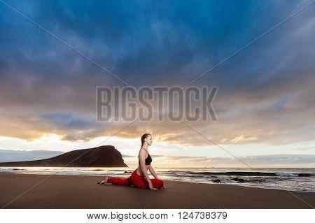 Summer sunrise yoga session on beautiful Playa de La Tejita beach with view on atlantic ocean and Punta Roja rock - tropical Tenerife island Canary in Spain. Cobra Pose Bhujangasana