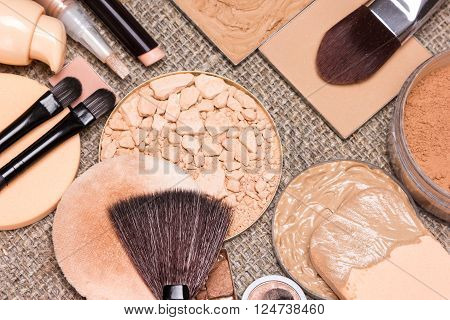 Basic makeup products to create beautiful skin tone and complexion. Correctors, foundation, powder, bronzer with brushes and cosmetic sponges on sackcloth