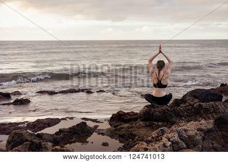 Summer sunrise yoga session on beautiful Playa de La Tejita beach with view on atlantic ocean and Punta Roja rock - tropical Tenerife island Canary in Spain. Meditation - lotus pose - padma asana