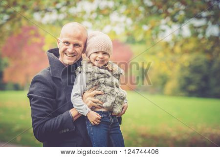 Daddy and daughter having fun in a beautiful autumnal park