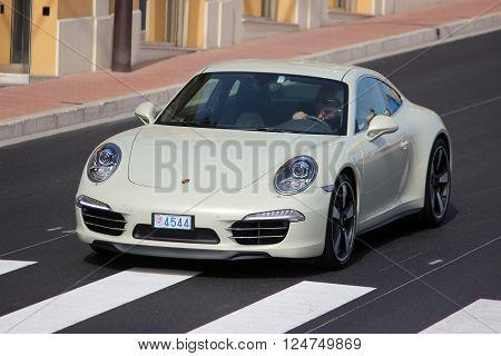 Monte-Carlo Monaco - April 6 2016: Porsche 911 Carrera S on Avenue d'Ostende in Monaco. Man Driving an Expensive White Porsche 911 50th anniversary edition in the south of France