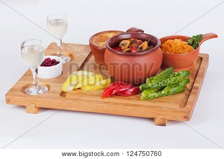 meat with mushrooms in a pot, julienne in a cocotte, pickles, pickled apples, vodka in a glass on a wooden board isolated white background food