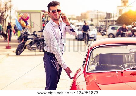 Young handsome man with phone opening red car door - Attractive businessman talking at phone is getting into sport vehicle - Successful male person using mobile technology outdoors - Lifestyle concept