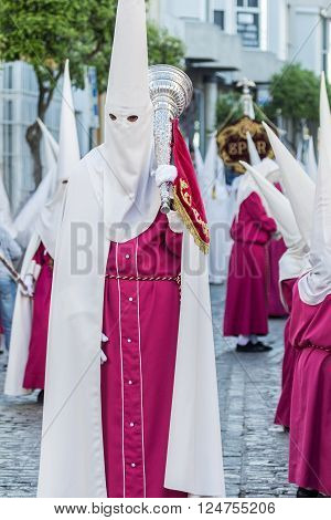 San Fernando, Spain - March 31, 2015: Penitent in white tunic holding a trumpet during Holy Week procession in San Fernando Cádiz Spain
