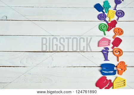 Notebook with  pencil on wooden background and fanny cartoon food.