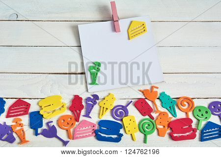 Color Toys on wooden background and fanny cartoon food.