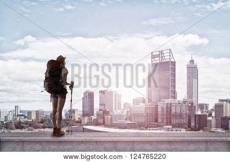 Young woman hiker standing on top of city building