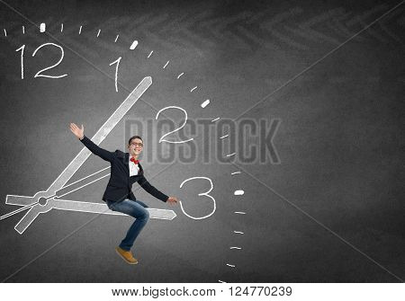 Young student guy in red glasses sitting on clock arrow