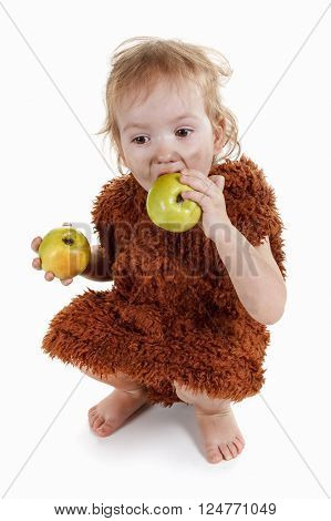 Little funny Neanderthal boy in a suit with a dirty face eating an apple. Humorous concept ancient caveman. On white background.