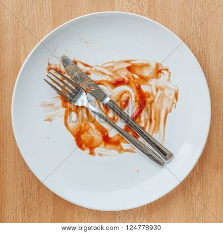 Top view of empty plate tomato sauce smeared on finished plate. Concept of tasty.