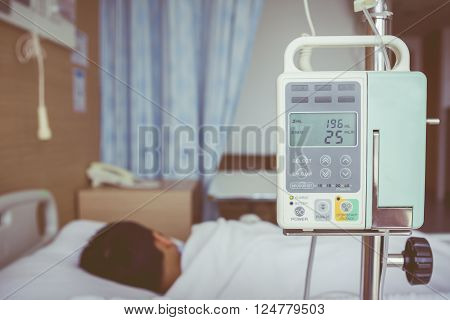 Illness asian boy lying on sickbed in hospital with infusion pump intravenous IV drip. Shallow depth of field, IV machine in focus, child out of focus. Health care and medical concept. Vintage style.