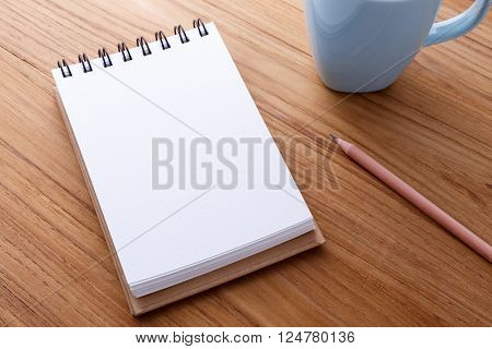 Spiral notebook with pencil and coffee mug on wood table