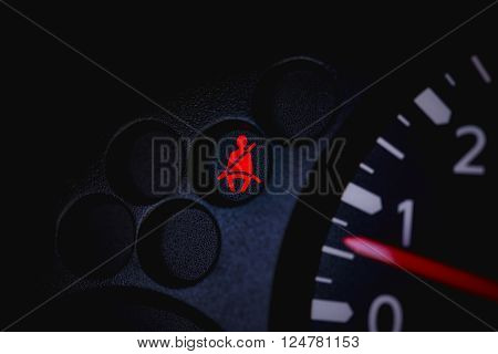 Car Dashboard showing the seat belt warning light