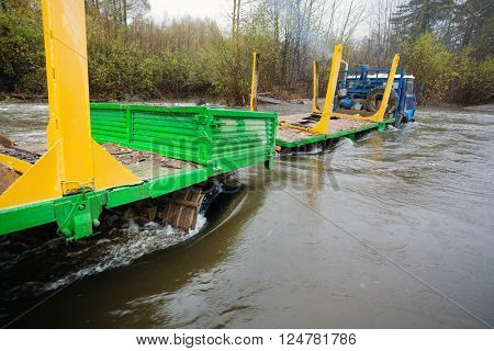 Heavy-duty truck for transportation of logs stuck in the river. Autumn rain. Russian Far East.