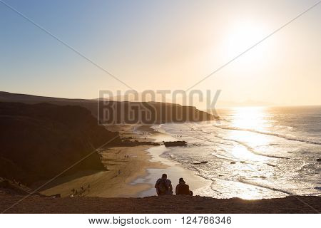 Couple watching surfers riding waves on La Pared beach at sunset, Fuerteventura, Canary Islands, Spain