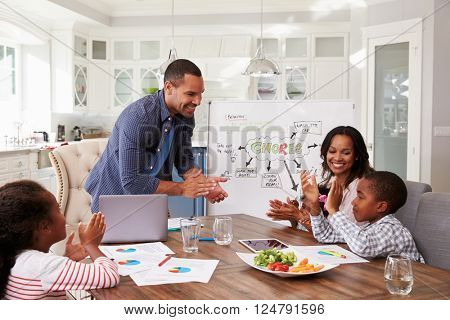 Family clapping at a domestic meeting in their kitchen