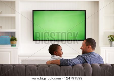Father and son watching TV looking at each other, back view
