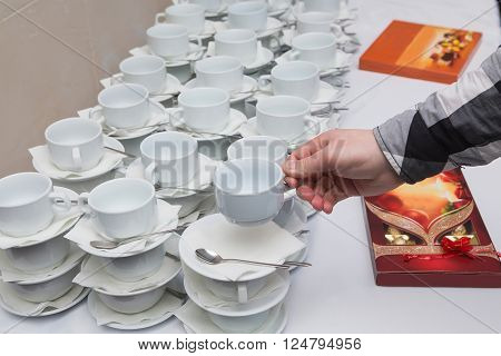 Many rows of coffee or tea cups for background. Men take a cup of tea