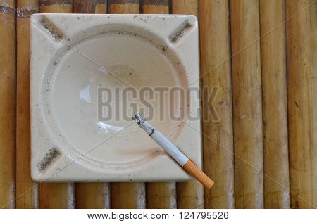 cigarette in tile ash tray on bamboo ** Note: Soft Focus at 100%, best at smaller sizes