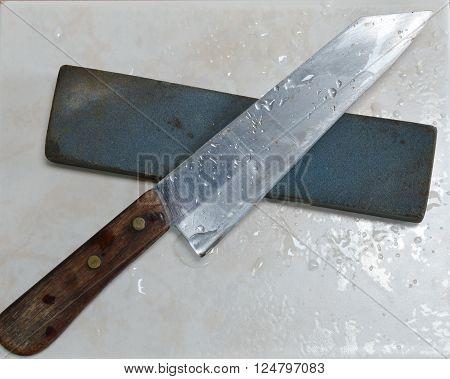knife and whetstone on white tile floor