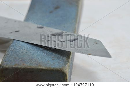 kitchen knife blade on grindstone in kitchen ** Note: Shallow depth of field
