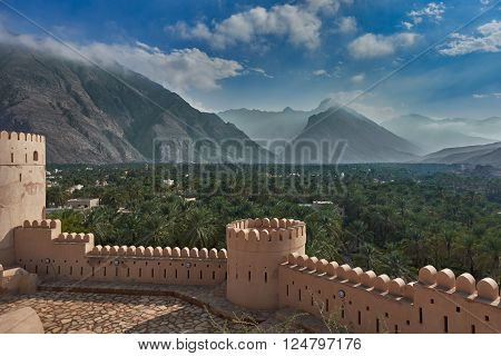 View from the top of a fort in Oman of mountains and date palms