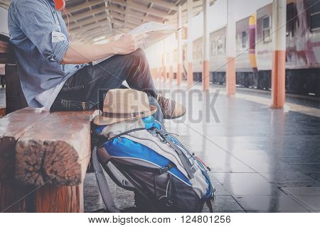 Side portrait of a young man traveler sitting with map choose where to travel and bag waiting for train vintage tone filter effected