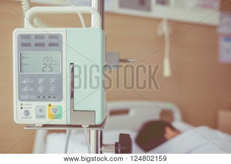 Illness asian boy lying on sickbed in hospital with infusion pump intravenous IV drip. Shallow depth of field, IV machine in focus. Health care and medical concept. Vintage style.