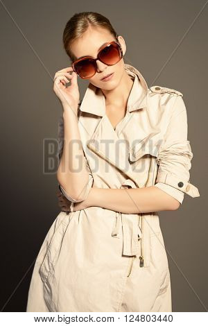 Fashion model posing at studio in a coat and sunglasses. Beauty, fashion. Business style.