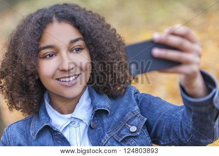Beautiful happy mixed race African American young woman girl teenager female child smiling with perfect teeth taking selfie photograph in fall or autumn