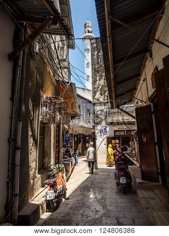 STONE TOWN ZANZIBAR - MAY 02 2015: One of the narrow streets in the old part of Stone Town Zanzibar in East Africa. Vertical orientation wide angle. Mosque's minaret in the background.