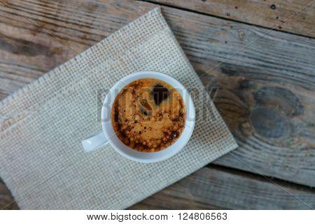 White cup of espresso macchiato on old wooden table. Cup of Espresso - stock photo.
