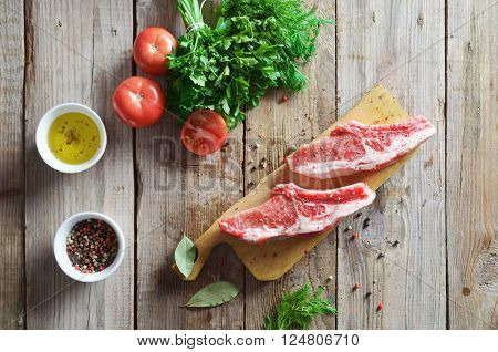 Raw meat for barbecue with fresh vegetables on wooden surface. Food, meat raw steak, beef steak bbq, tomatoes, peppers, spices for cooking meat.
