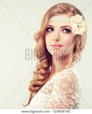 Beautiful model in lace dress with a pigtail ,   lace  flower barrette .  Hairstyle braid .   Bride in white wedding dress