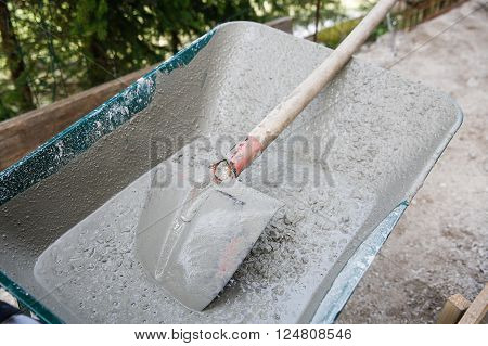 Dirty wheelbarrow containing concrete mix for foundation building. Construction business and tools, do-it-yourself, manual work, teamwork concept.