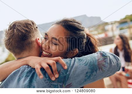 Woman greeting her boyfriend and embracing. Young woman welcoming her friends at party. Young friends arriving at rooftop party.