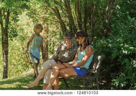 3 Generations. Grandmother mother and son in garden. The women are sitting on a bench and looking at a tablet. Grandmother is smiling. Young boy is carrying a butterfly net and peeking at the tablet.