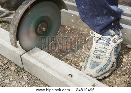 Construction worker cutting a reinforced concrete pillar for installation with professional machine. Construction business, do-it-yourself, dirty and dangerous work around the house concept.