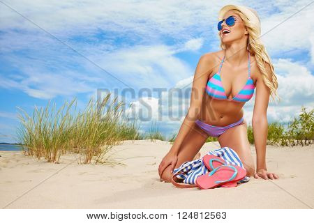 summer holidays, vacation and beach concept - girl in bikini and shades on the beach